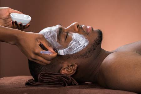 -face-mask-to-young-african-man-in-spa